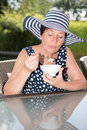 Attractive woman siiting by the pool and eating a bowl of fruit Royalty Free Stock Photo