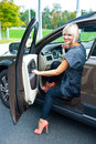 Attractive woman sitting in her car blond high heels Royalty Free Stock Photography
