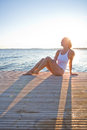 Attractive woman sitting on pier in white bathing suit wooden in nordic country during summer Stock Photos