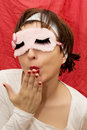 Attractive woman in sleep mask sending kiss caucasian sleeping Stock Photography
