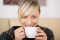 Attractive woman smiling with a cup of coffee blond behind in shop Royalty Free Stock Photo