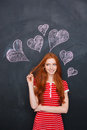 Attractive woman standing over blackboard with drawn hearts behind her