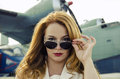 Attractive woman in sunglasses outside near military plane redhead adult Royalty Free Stock Image