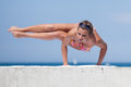Attractive woman in swimwear doing yoga at the sea young bikini Stock Photography