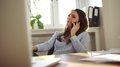 Attractive woman talking on mobile phone from her desk young sitting at pretty caucasian businesswoman working in home office Royalty Free Stock Image