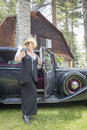 Attractive woman in twenties outfit near antique a young automobile Stock Photo