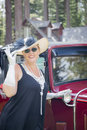 Attractive woman in twenties outfit near antique a young automobile Stock Image