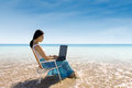 Attractive woman typing on laptop at beach working with the Stock Image