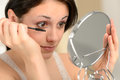 Attractive woman using mascara and handheld mirror on her eyelashes holding Stock Photography