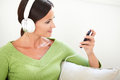 Attractive woman using a portable music player Royalty Free Stock Photo