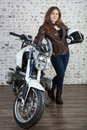 Attractive woman in vintage outfit holds white helmet, standing near motorcycle, brick wall background Royalty Free Stock Photo