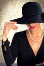 Attractive woman wearing black dress, hat and pearls Royalty Free Stock Photo