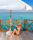 The attractive woman in white bikini sunbathes on a wooden terrace Royalty Free Stock Photo