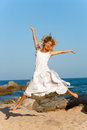 Attractive woman in white jumping outdoors. Stock Photo