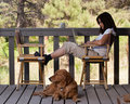 Attractive woman on wooden deck with dog and laptop an relaxing a her working her Stock Photography