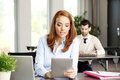 Attractive woman at work portrait of efficiency sales women sitting office behind her laptop and holding hands digital tablet Stock Photography