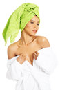 Attractive woman wrapped in towel with turabn she is showing her shoulders isolated on white Royalty Free Stock Image