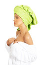 Attractive woman wrapped in towel with turban trying to undress her side view isolated on white Stock Photo