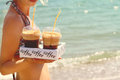 Attractive women holding two ice frappe coffee on the beach near sea Stock Photos
