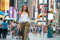 Attractive young adult woman walking around crownd on New York City street and carrying a bag wearing white top Royalty Free Stock Photo