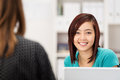Attractive young asian office worker sitting at her desk in the chatting to a female co and smiling at the camera Stock Photos