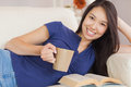 Attractive young asian woman lying on the sofa reading a novel and drinking hot beverage in living room at home Royalty Free Stock Photos