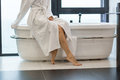 Attractive young barefooted woman in white bathrobe sitting on bathtub Royalty Free Stock Photo