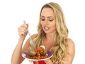 Attractive Young Blonde Haired Woman Eating a Freshly Baked Jacket Potato with Baked Beans Royalty Free Stock Photo