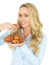 Attractive young blonde haired woman taking a danish pastry from a plate of assorted pastries in her twenties mixed freshly baked Royalty Free Stock Photos