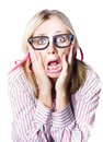 Attractive young blonde woman wearing nerdy glasses reacting in horror and fright with her eyes wide and her hands clawing at her Royalty Free Stock Images