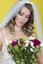 Attractive young bride holding wedding bouquet flowers beautiful shot against yellow background looking at romantically and Stock Photo