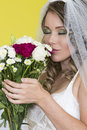 Attractive young bride holding wedding bouquet flowers beautiful tenderly smelling taking in the scent with eyes closed Stock Photo