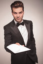 Attractive young business man offering you a invitation. Royalty Free Stock Photo