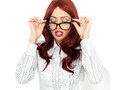 Attractive young business woman peering over her glasses with long red hair in twenties as if studying some reading matter or Royalty Free Stock Images