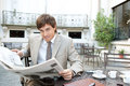 Attractive young businessman reading newspaper having coffee sitting coffee shop terrace classic office buildings city square Stock Photography
