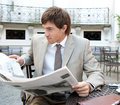 Attractive young businessman reading newspaper having coffee sitting coffee shop terrace classic office buildings city square Royalty Free Stock Photo