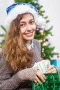 Attractive young Caucasian woman taking dollars cash in hands from green bag at Christmas eve Royalty Free Stock Photo