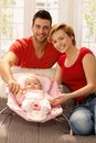 Attractive young couple with baby girl family portrait of newborn smiling looking at camera Stock Photography