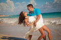 Attractive young couple on the beach honeymoon romantic in love at sunrise newlywed happy embracing enjoying ocean sunrise during Stock Photo