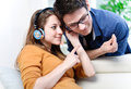 Attractive young couple listening music together in their living natural portrait of room at home Royalty Free Stock Photo