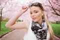 Attractive young female model posing at spring park casual woman wearing sunglasses and scarf looking camera Royalty Free Stock Images