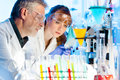 Attractive young female scientist and her senior male supervisor looking at the cell colony grown in the petri dish in the life Stock Photography
