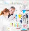 Attractive young female scientist her senior male supervisor observing color shift red liquid glass tube life science research Stock Image