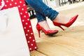 Atraktívne mladý žena v vysoký podpätky teší rozbiť po úspešný nakupovanie
