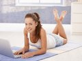 Attractive young female using laptop at home downloading e mails laying on floor smiling Royalty Free Stock Images