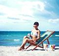 Attractive young girl in bikini sunbathing on beach. Traveling, Royalty Free Stock Photo