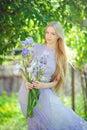 Atraktivní mladý blondýnka vlasy přírodní vonící modrý purpurová kosatec květiny na venku nabídka