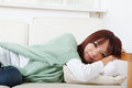Attractive young girl lying on sofa and looking at you in house Royalty Free Stock Photo