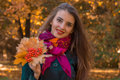 Attractive young girl in pink scarf keeps leaves from Rowan in his hand and smiling close-up Royalty Free Stock Photo