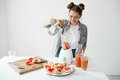 Attractive young girl smiling adding water in blender with grapefruit pieces and rosemary. Healthy diet food nutrition.